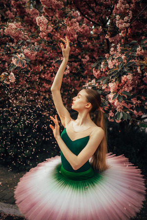 Ballerina dancing in a beautiful tutu against the background of flowering sakura trees and falling petals in the park. Closeup.