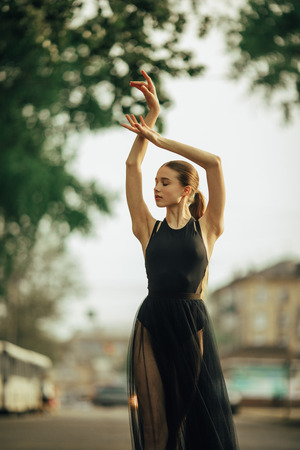 Ballerina dancing in a black transparent dress against the background of city street. Closeup.