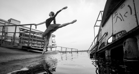 Ballerina standing in arabesque pose in tutu on the background of river, pier and old boat. Black and white image. Stock Photo