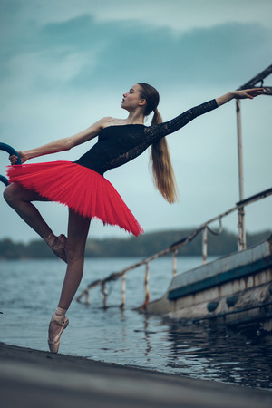Ballerina is dancing on the coast of river in a black and red tutu against background of old boat.