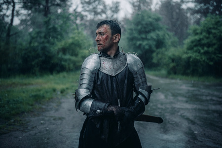 A young man stands in the image of a medieval knight in armor and with a sword in his hands in the rain.