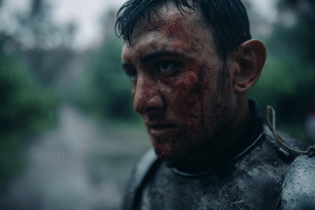 Portrait of young man in the image of a medieval knight in armor with blood and wounds on his face in the rain. Stock Photo