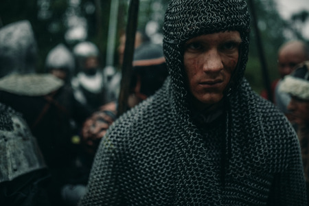 Portrait of young man in the image of a medieval knight in chain armor on background of his combat squad.
