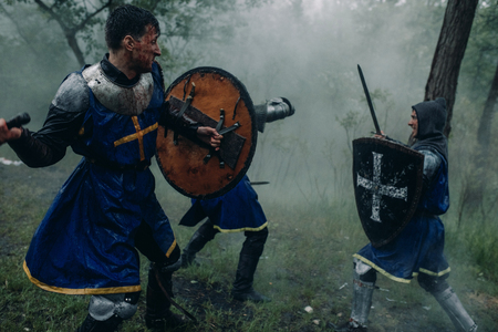 Threee young men in the image of a medieval knights crusaders in armor fight with swords against the backdrop of a misty forest. Stock Photo