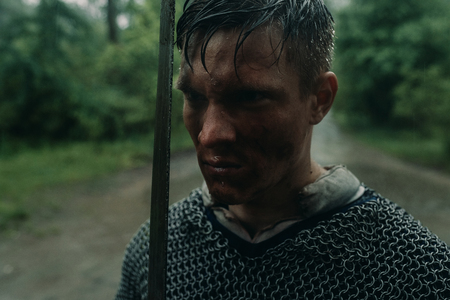 Portrait of young man in the image of a medieval knight in chain armor and with a sword in his hands in rain.