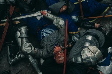 Los cruzados de los caballeros medievales asesinados yacen en el suelo en el campo de batalla. Vista superior.