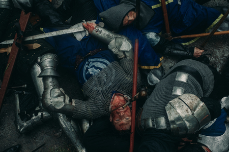 The murdered medieval knights crusaders lie on the ground on the battlefield. Top view. Banco de Imagens - 124432090