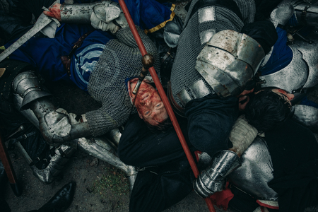 The murdered medieval knights crusaders lie on the ground on the battlefield. Top view.