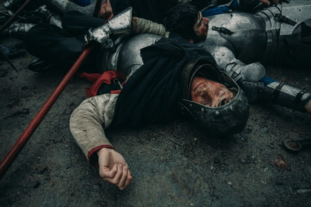 The murdered medieval knights crusaders lie on the ground on the battlefield. Stock fotó