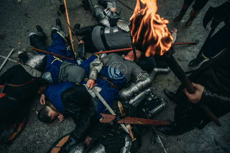 The murdered medieval knights lie on the ground on the battlefield. Nearby are the winners with burning torch.