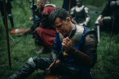 A young man sits in the image of a medieval knight in armor and cleans his sword during the halt in the camp.