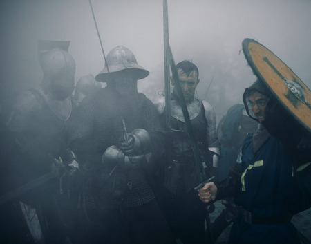 Combat squad of medieval knights of the Crusaders stand in armors and helmets with their swords and shields preparing to attack in misty morning.