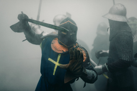 Combat squad of medieval knights of the Crusaders are in armors and helmets during the battle with swords in misty morning.