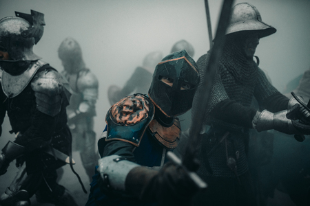 Combat squad of medieval knights of the Crusaders are in armors and helmets during the battle with swords in misty morning. Banco de Imagens - 124432237