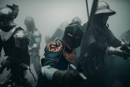El escuadrón de combate de los caballeros medievales de los cruzados están en armaduras y cascos durante la batalla con espadas en la mañana brumosa.