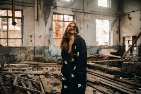 Young lonely sad woman stands in the middle of an abandoned and destroyed building. Stock Photo