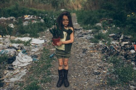 A homeless girl is standing on a garbage dump with a houseplant in a pot. The concept of environmental pollution and landfill reclamation. The concept of poverty and homelessness.
