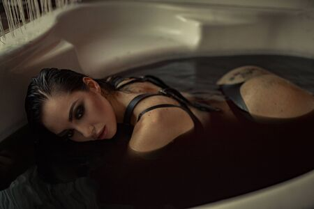 Woman in black lingerie takes a bath in colored black water. Back view.