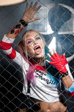 Dnipro, Ukraine - August 17, 2016: Girl in costume Harley Quinn. She stands near grid and licks its. Close up. Cosplay.