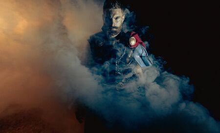 Dnipro, Ukraine- June 5, 2019: Cosplayer portrays superhero Thor from Marvel Comics against smoke background.