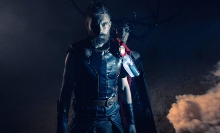 Dnipro, Ukraine- June 5, 2019: Cosplayers portray superhero Thor and goddess of death Hela from Marvel Comics against smoke background.