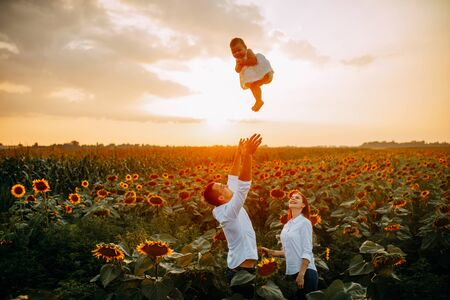 Happy young parents with baby have a fun, play and throw up their baby in the sunflower field at sunset against sky background.