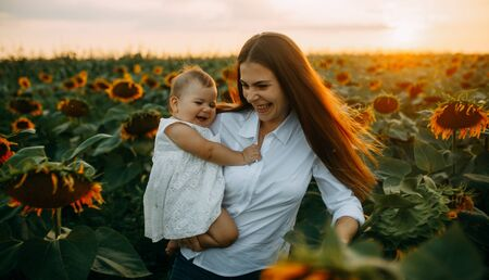 Happy young mother with baby are having a fun and walking in the sunflower field at sunset. Standard-Bild