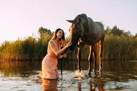 A young smiling woman sits next to the horse that produces splashes on the water at sunset. Backlight.