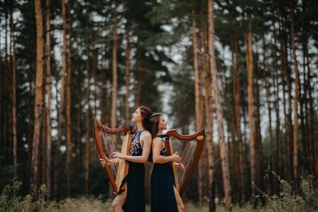 Two women harpists stand at forest and play harps in beautiful dresses against a background of pines.
