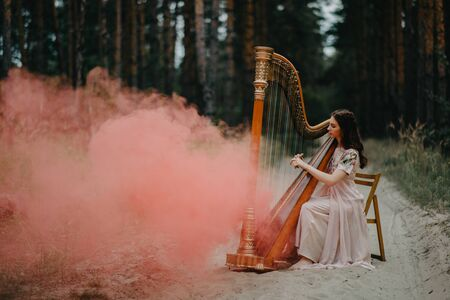 Woman harpist sits at forest road and plays harp against a background of pines and pink smoke.