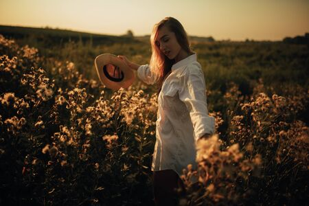 Happy young woman in white shirt is walking with pleasure among the flowers and grass on meadow at sunset.