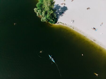 Shooting from the drone of the coastline with a beach, people swimming in the water and a floating kayak.