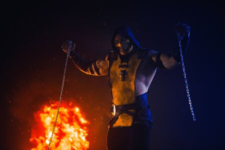 Dnipro, Ukraine - September 29, 2019: Cosplayer portraying Scorpion from the video game Mortal Kombat with chains in his hands poses at the fire background.
