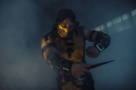 Dnipro, Ukraine - September 29, 2019: Cosplayer portraying Scorpion from the video game Mortal Kombat with dagger in his hand poses at the smoke background.