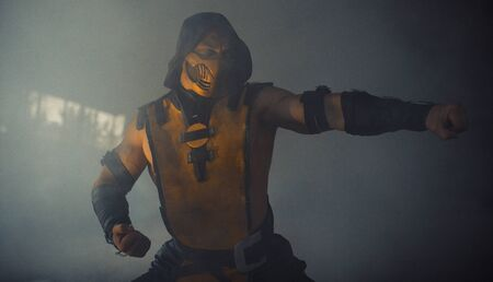 Dnipro, Ukraine - September 29, 2019: Scorpion Cosplayer from the video game Mortal Kombat poses at the smoke background.