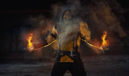 Dnipro, Ukraine - September 29, 2019: Cosplayer portraying Scorpion from the video game Mortal Kombat with flame from his hands poses at the smoke background.