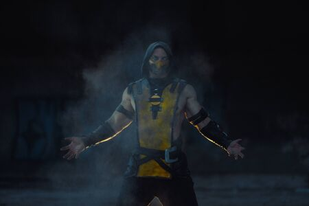 Dnipro, Ukraine - September 29, 2019: Cosplayer portraying Scorpion from the video game Mortal Kombat poses at the smoke background.