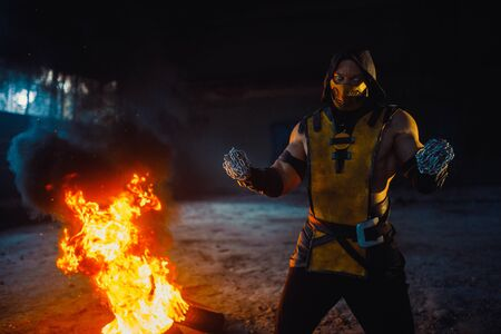 Dnipro, Ukraine - September 29, 2019: Cosplayer portraying Scorpion from the video game Mortal Kombat with chains in his hands poses at the fire and smoke background. Publikacyjne