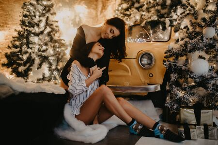Lesbian couple sits and hugs against the background of Christmas decorations and a yellow retro car. Zdjęcie Seryjne - 133813260