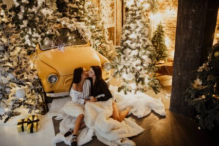 Lesbian couple sits on a fur rug and kisses against the background of Christmas decorations and a yellow retro car.