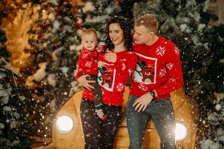 Happy family with little son stands against background of Christmas tree, retro car and snowfall. Zdjęcie Seryjne