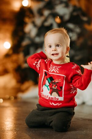 Little boy sits on floor against background of Christmas tree nd decorations. Zdjęcie Seryjne - 136099051