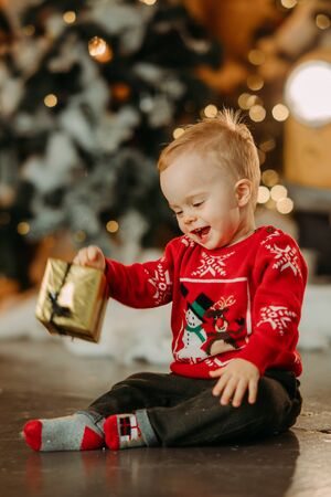 Little boy sits on floor with gift box in his hand against background of Christmas tree nd decorations. Zdjęcie Seryjne - 136099053