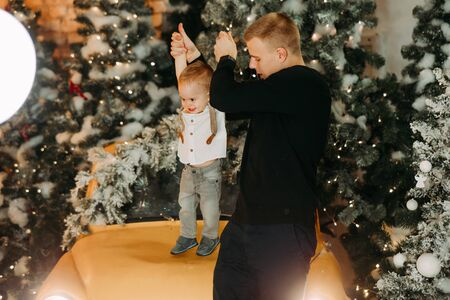 Father plays with his little son against background of Christmas tree nd decorations.