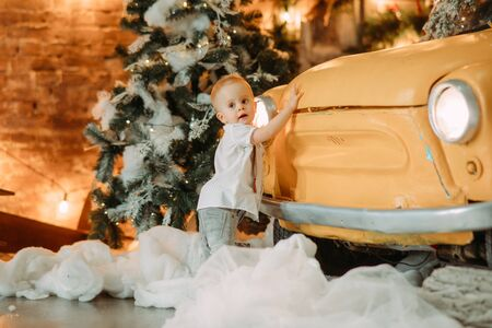 Little boy stands next to retro car against background of Christmas tree and decorations.