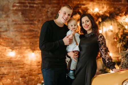 Happy family poses against background of Christmas tree and decorations. Zdjęcie Seryjne - 136099066