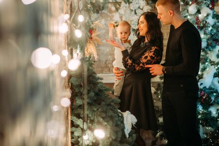 Happy family stands against background of Christmas tree and decorations.