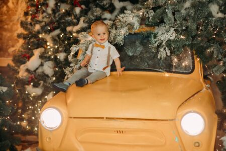A little boy sits on the hood of a retro car against the background of a Christmas tree and decorations.