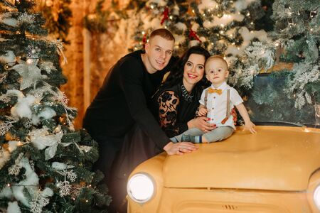 Happy family poses against background of Christmas tree, decorations and retro car. Zdjęcie Seryjne