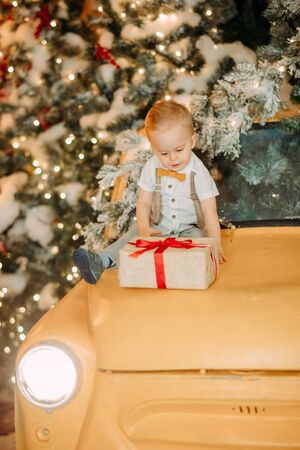 A little boy sits on the hood of a retro car with gift box in his hands against the background of a Christmas tree and decorations.